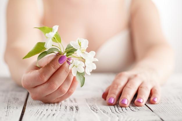 リンゴの木の花を保持しているマニキュアで女性の手。リンゴや桜の春の花。