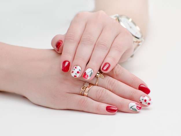 Female hands with manicure, red nail polish, drawing with cherries