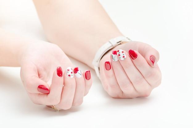 マニキュア、赤いマニキュアで女性の手。白 。 Premium写真