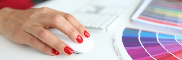 Female hands with manicure works at the computer