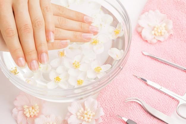 Женские руки с маникюром и инструментами на полотенце