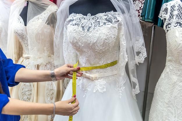 測定テープとウェディングドレスの女性の手