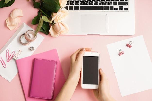 携帯電話、ノートパソコン、ピンクのクラフト用アイテムを持つ女性の手