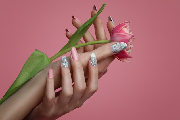 Female hands with nails art design and spring flower