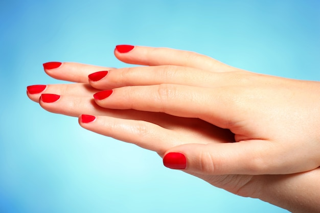 Female hands with nails painted in red over blue background