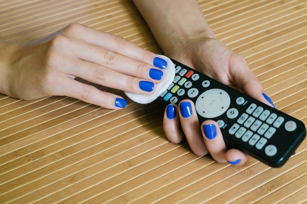 Female hands with a napkin wipe the remote control at the wooden table