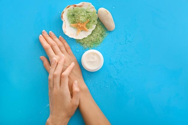 Женские руки с натуральным кремом и морской солью на цветном фоне