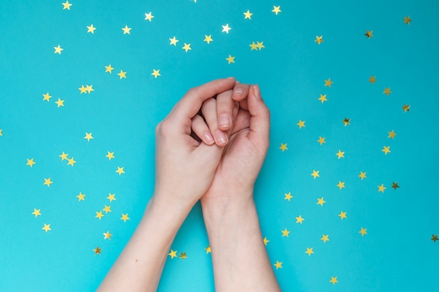 Female hands with nude manicure on blue wall with scattered gold stars. festive wall. concept of naturalness.