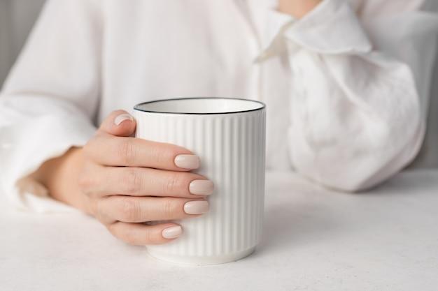 Женские руки с обнаженным дизайном ногтей, держа чашку горячего напитка концепция салона красоты маникюра