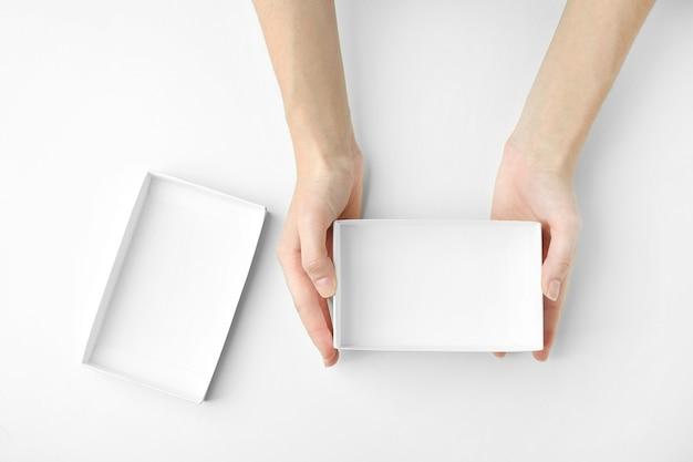 Женские руки с открытой коробкой на белой поверхности