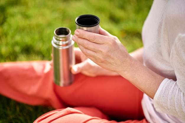 Female hands with open thermos on lawn