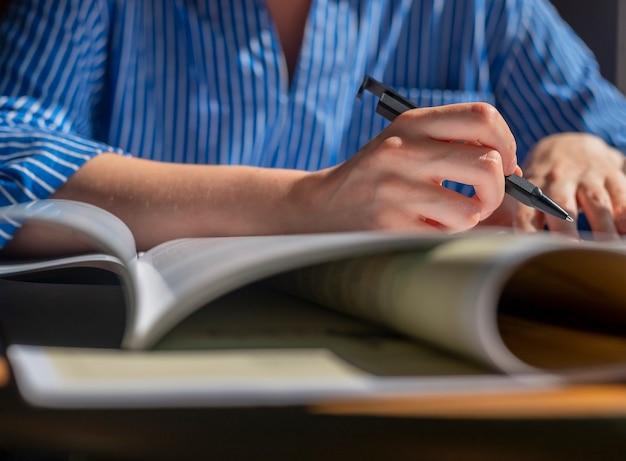 Женские руки с ручкой крупным планом, писать в записной книжке, делая заметки, изучая
