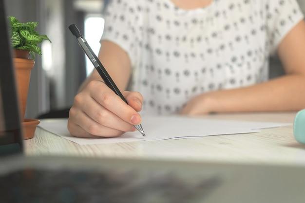 文書にペンで書いている女性の手。オフィスデスクワークスペースの背景写真
