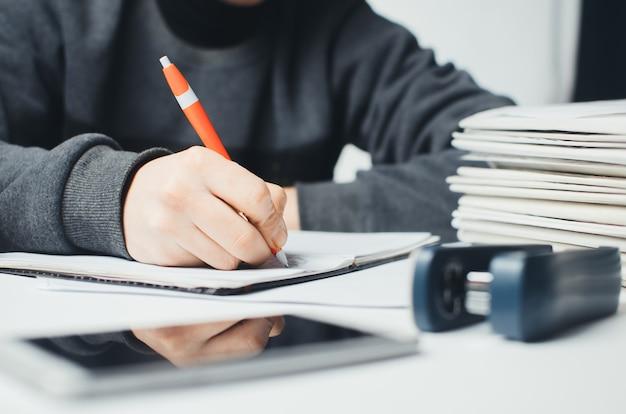 ノートにペンで書く女性の手