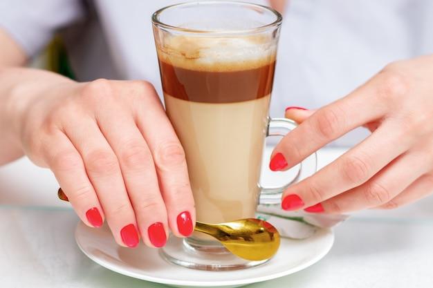 Женские руки с идеальным красным маникюром держит чашку кофе капучино крупным планом.