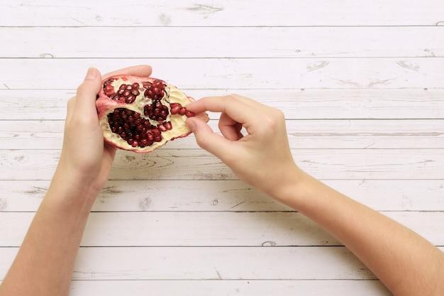 Женские руки с кусочком граната, принимая зерно фруктов на белом деревянном фоне.