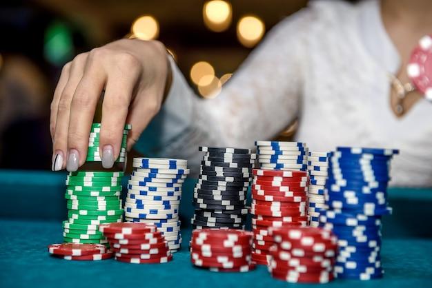 ポーカー チップのクローズ アップの山を持つ女性の手