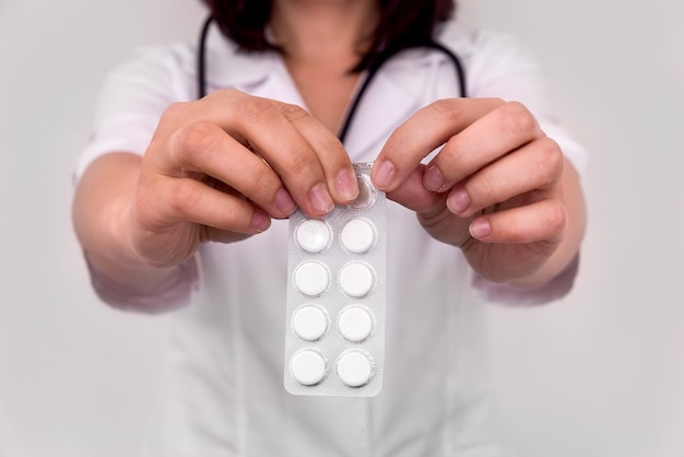 Female hands with pills in blister, closeup