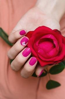 ピンクのネイルアートと女性の手。