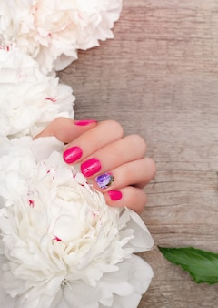 Female hands with pink nail design holding white peonies