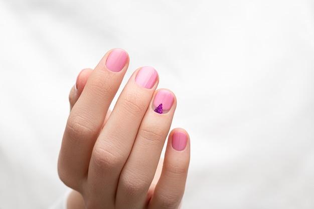 白い布の背景にピンクのネイルデザインと女性の手。