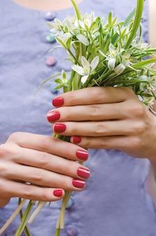 ピンクのネイルデザインと女性の手