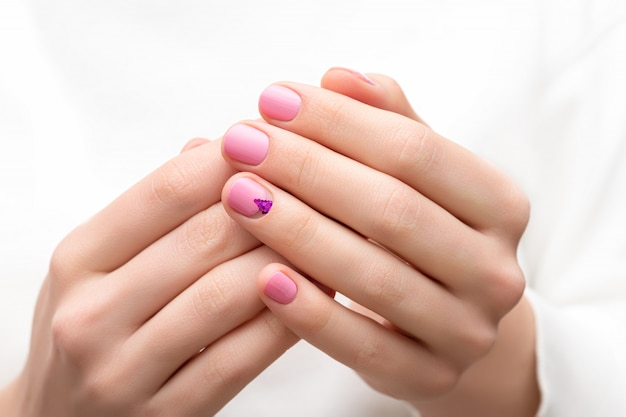 ピンクのネイルデザインの女性の手。