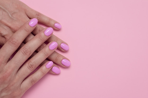Female hands with pink nail polish, glamorous manicure.