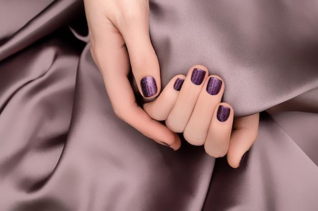女性手有紫色指甲设计。闪亮的紫色指甲油。女人手放在粉红色的织物背景上。