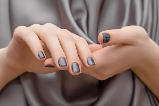 女性手有紫色指甲设计。闪亮的紫色指甲油。女人手放在紫色的织物背景上