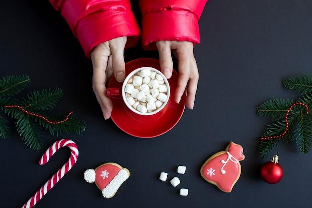 黒の背景に赤いカップホットチョコレートと女性の手。クリスマス作文。上面図。
