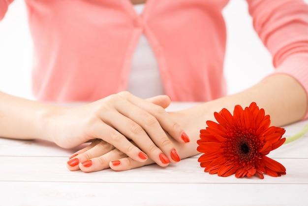 Женские руки с красным маникюром и открытой бутылкой лака на столе