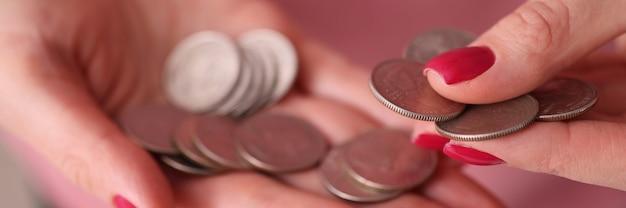 コインのクローズアップを数える赤いマニキュアと女性の手。ポケット経費の概念