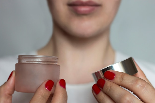 Female hands with red manicure hold an open jar with cream. the concept of facial care. selective focus
