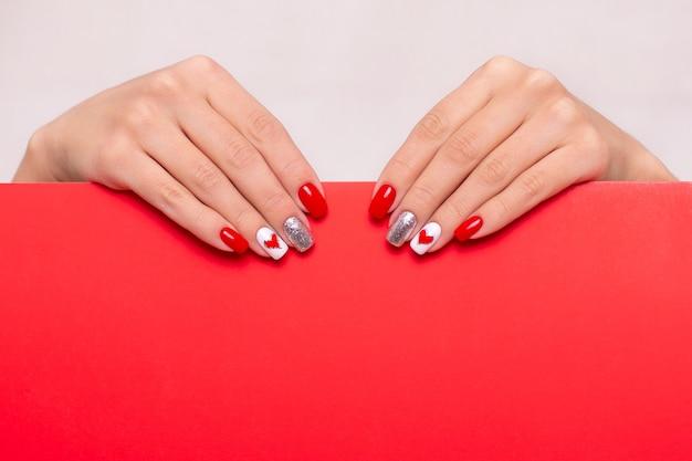 Женские руки с красными ногтями маникюра, дизайн сердца