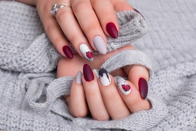 赤いマニキュアの爪を持つ女性の手