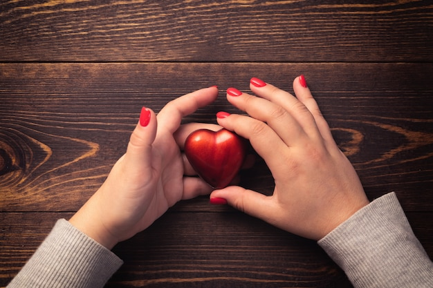 Female hands with red nails holding heart on wooden background.