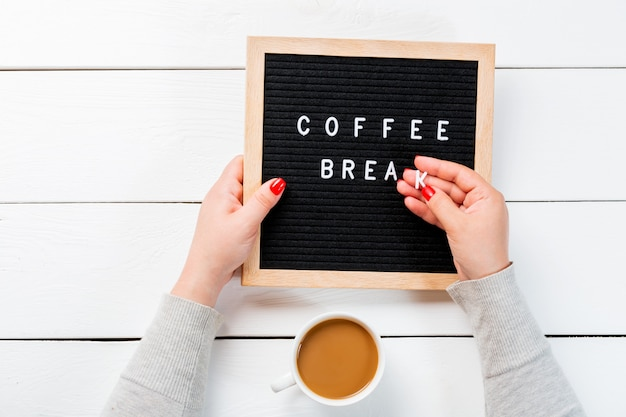 Female hands with red nails holding a letter board with words coffee break near cup of coffee over white wooden table. top view
