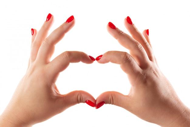 白で隔離される心臓の形で赤い爪を持つ女性の手