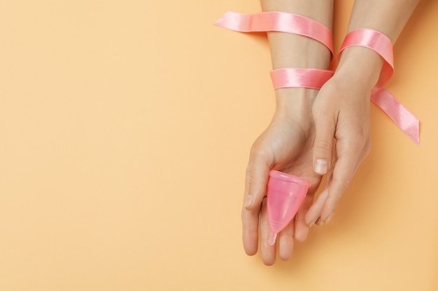 Female hands with ribbon hold menstrual cup on beige background