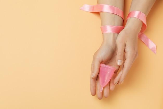 리본으로 여성의 손을 잡고 베이지 색 배경에 생리 컵