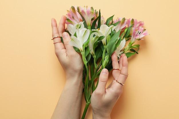 Женские руки с кольцами и цветами альстромерии на бежевом фоне