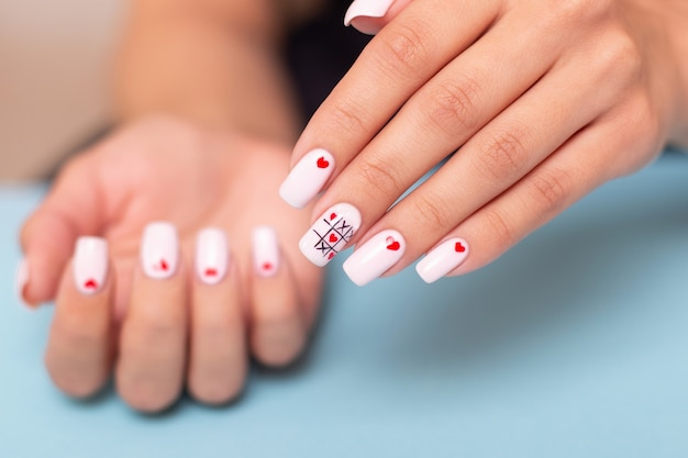 Female hands with romantic manicure nails, hearts design