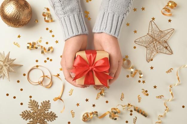 밝은 배경에 작은 선물 상자와 크리스마스 장식이 있는 여성 손