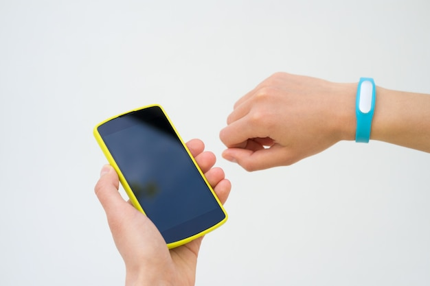 Female hands with a sports bracelet and smart phone close up on a white background