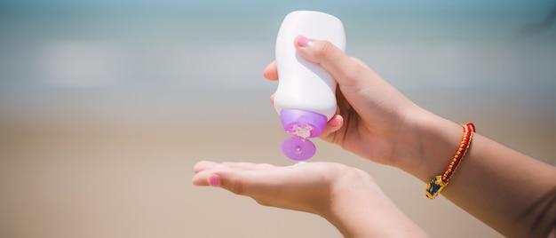 해변에서 태양 보호 크림과 함께 여성 손. 피부 관리 개념