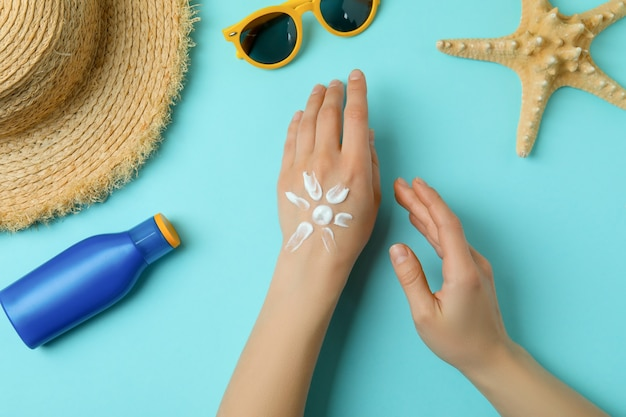 Female hands with sunscreen on blue with summer accessories