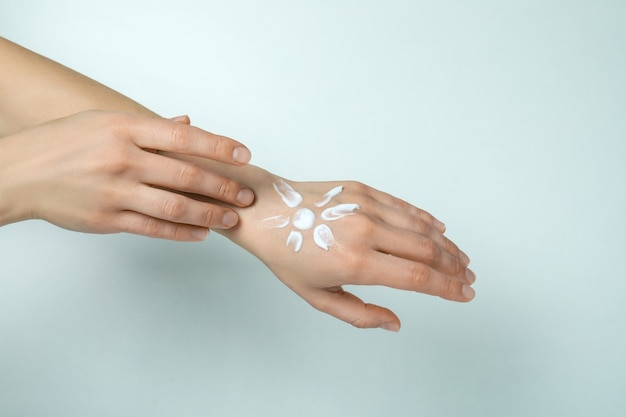 Female hands with sunscreen on white