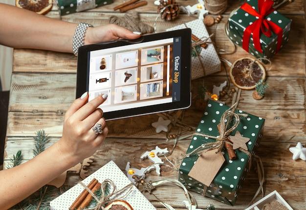 Женские руки с планшетом на столе с рождественскими украшениями ручной работы