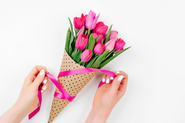 Female hands with tulips bouquet. beautiful spring pink flowers.